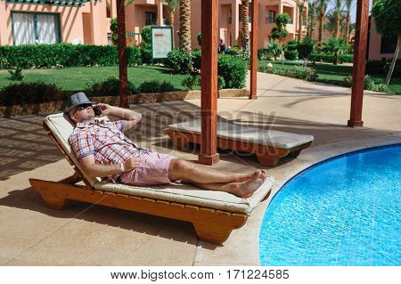man in a hat lying on a lounger and talking on the phone.