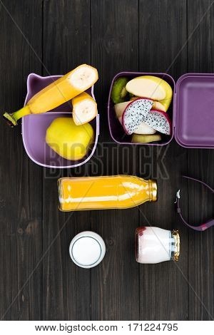 Natural vitamins. Two lunch boxes with fruits inside standing on black table, glass bottle with orange juice and yoghurt lying