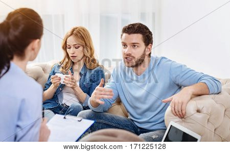 Dealing with problems. Depressed unhappy young couple having an appointment with a psychologist and describing their problems to her while looking for a solution