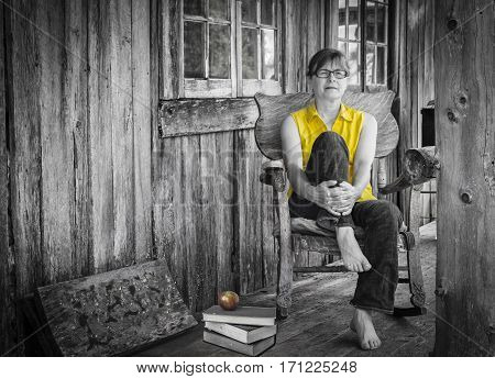 horizontal black and white image of a caucasian woman wearing a bright yellow shirt relaxing on an old wooden rocking chair in front of a very old wood house.