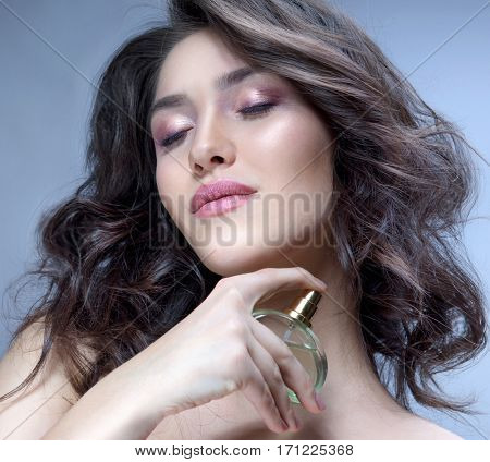 beauty portrait of attractive young caucasian woman brunette on blue background studio shot applying perfume face skin makeup eyes closed