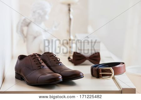 Brown leather men's shoes with belt, bow-tie. Set groom accessories. Soft focus