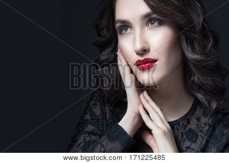 Beauty Brunette Woman with Perfect Makeup. Beautiful Professional Holiday Make-up. Red Lips , perfect eyebrows. Beauty Girl's Face isolated on dark background.