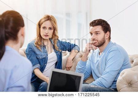 Psychological advice. Nice thoughtful pleasant couple sitting thoughtfully and listening to the psychologist while dealing with their problems