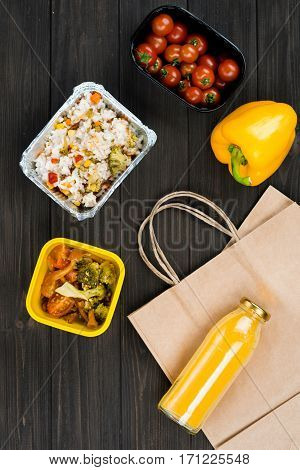 Stewed rice. Flat lay picture of yellow pepper lying near box with tomatoes, two boxes with stewed dish standing in the middle