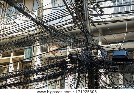 Chaos of cables and wires on electric pole in Bangkok Thailand