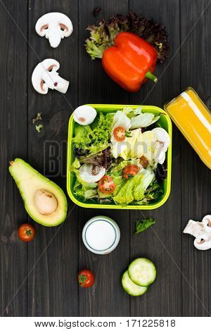 Fresh vegetables. Flat lay picture of big green box standing in the middle of the picture, half of avocado mushrooms and tomatoes lying around this box