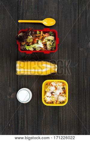 Accent on yellow. Flat lay picture of orange juice in bottle lying between lunch boxes, yellow spoon is situated near salad