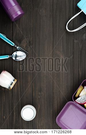 Perfect details. Violet thermos and blue paper-bag lying parallel to jar with yoghurt