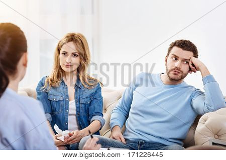Being bored. Pleasant nice bearded man sitting near his wife and looking away while being not willing to participate in discussion