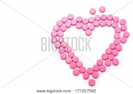 Heart shape of pink pills on white background. Tablets of drug for asthma treatment.