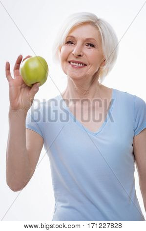 Healthy lifestyle. Delighted beautiful woman looking straight at camera keeping smile on the face posing with green apple in right hand over white background