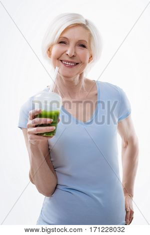 Drink this. Happy smiling female expressing positivity holding left hand on the waist while keeping apple juice in right hand