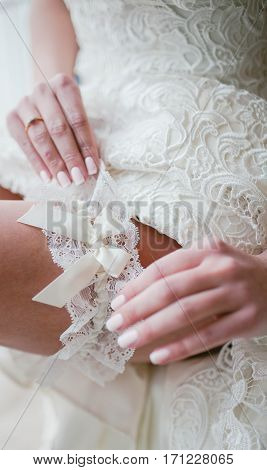 The bride putting on garter. Wedding day