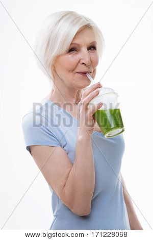 It is tasty. Delighted female looking straight at camera keeping smile on the face while trying fresh juice standing in semi position over white background
