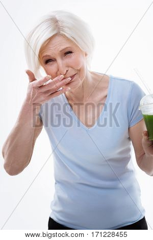 Do not drink it. Beautiful aged female squinting her eyes keeping fingers near her mouth while standing over white background
