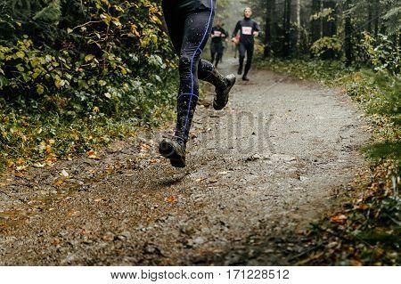 athlete runner runs marathon forest trail feet in mud