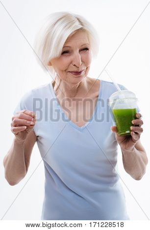 Express emotions. Portrait of sincere aged woman making a face while trying smoothie, standing over white background