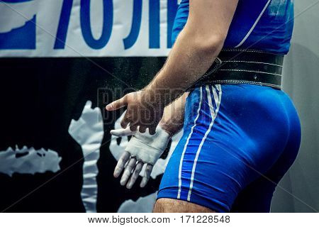 male athlete powerlifter hands in chalk on competition powerlifting