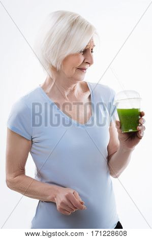 Awful taste. Grey haired woman expressing disgust while looking at the glass with sour smoothie, standing in semi position