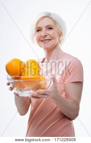 Fount of vitamins. Kind smiling female wearing pink tee shirt holding big nesting bowl with appetizing oranges posing over white background