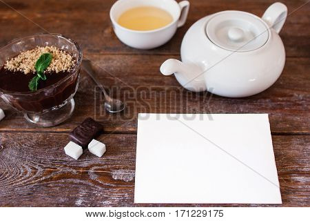 Blank card with teapot and dessert on table. Top view on wooden table with set for drinking tea and chocolate cream with white empty sheet of paper, free space
