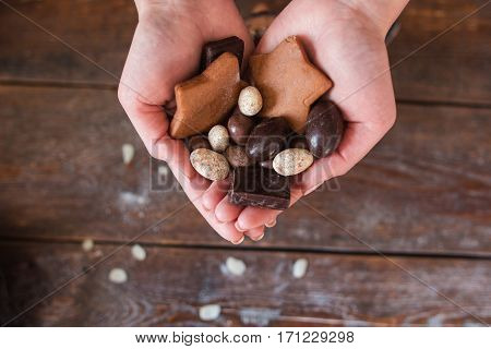 Handful of chocolate sweets flat lay. Top view on female hands with cookies and nuts, Sweet tooth, confectionery, passion, dessert concept