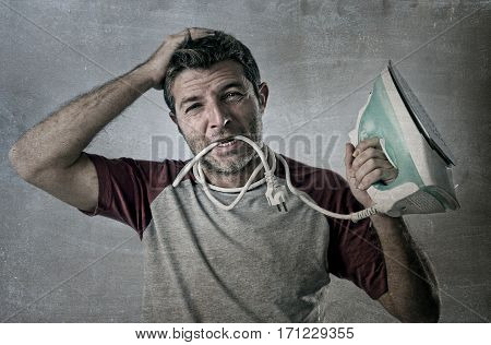 young crazy desperate and frustrated man doing housework holding iron and cable in mouth stressed and confused in unskilled and unable male for ironing isolated on even background