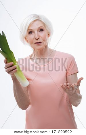 It is your choice. Competent in healthy food pensioner female pointing you with left hand keeping big green leek, standing over white background