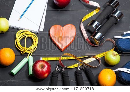 Heart fruit and dumbbells. Fitness healthy lifestyle on a black wooden background