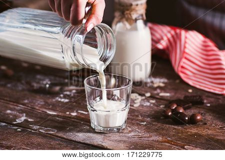 Pouring new milk into glass closeup. Fresh rustic beverage, drinking organic milk. Healthy lifestyle, natural product, vitamins for children concept