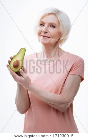 Favorite ingredient. Delighted aged female wearing pink T-shirt keeping half of ripe avocado in her hands, standing over white background