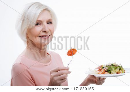 Mix of salad. Delighted healthy mature female turned her head to camera while keeping fork with tomato in right hand and holding plate with salad in left hand, isolated on white background