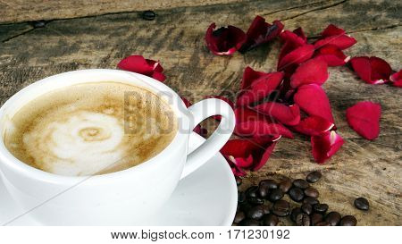 Rose and cappuccino coffee. A cup of latte, cappuccino or espresso coffee with milk put on a wood table with dark roasting coffee beans. Drawing the roses by foam milk on top.