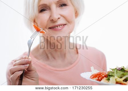 Dinner time. Delighted healthy mature female keeping fork with tomato in right hand and holding plate with salad in left hand looking straight at camera, isolated on white background