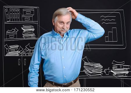 Lots of work. Pleasant optimistic senior man standing in his office and scratching his head while having a heavy workload