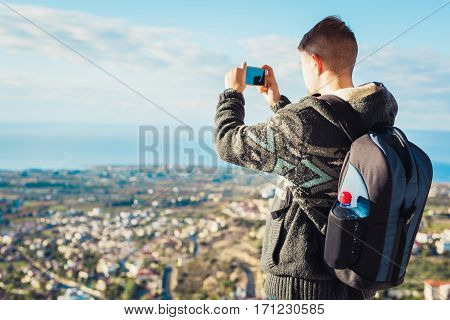 Traveler man taking photographs town with smartphone