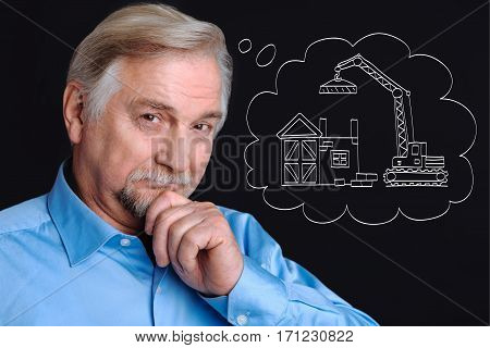 Building engineering. Intelligent positive elderly man putting his hand to the chin and smiling while thinking about his new building project