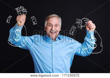 I am rich. Happy cheerful elderly man holding bags with money and smiling while standing against the black background