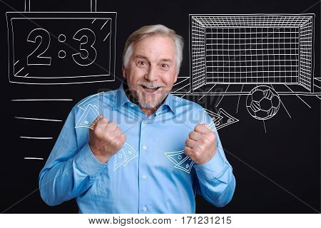 Sports betting. Joyful happy aged man holding banknotes and laughing while having a winning bet