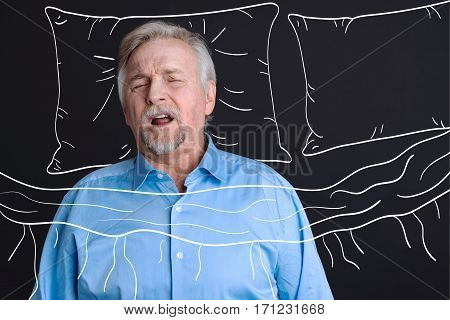 Sweet dreams. Nice pleasant aged man lying on a pillow and yawning while sleeping in his bed