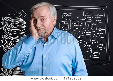 So much work to do. Unhappy stressful aging man putting his hand to the cheek and felling unhappy while having lots of work