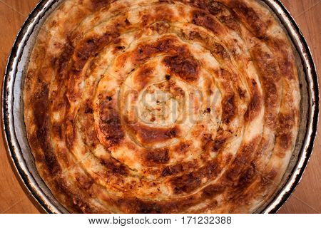Traditional Bosnian Turkish dish pork pie pie in the pan on a nice wooden background