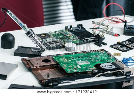 Electronic repairman workplace with components. Disassembled CPU in repair shop, tools and other parts of computer. Electronics development, hobby, business concept