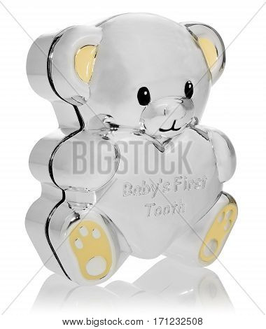 Silver box in the shape of a teddy bear to the first baby teeth. Closed box at an angle. Ears and feet in yellow on a white background with slight reflection.