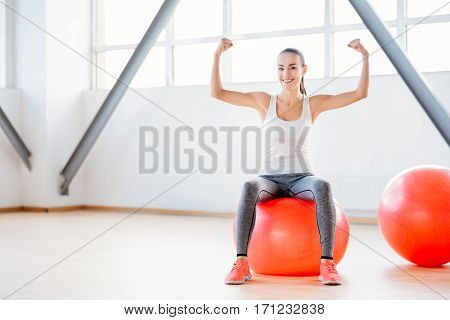 I like sport. Strong joyful well built holding her hands up and showing her muscles while sitting on the fitness ball