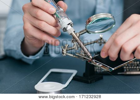 Soldering broken smartphone in repair shop closeup. Repairman hands working with disassembled mobile phone and work tolls. Electronic fixing, modern technology, business concept