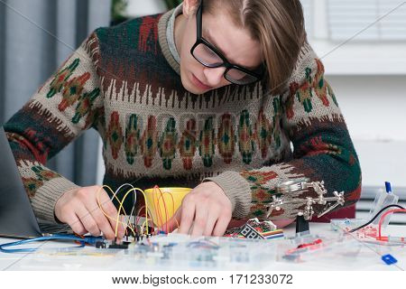 Young man intently working with electronic parts. Geek connecting colorful wires to breadboard at workshop. Electronic development, construction, diy, hobby concept