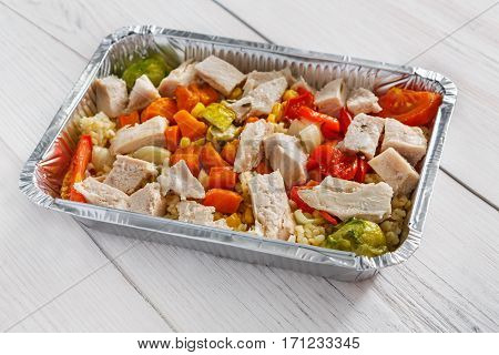 Healthy food restaurant delivery and diet concept. Take away of fitness meal. Weight loss lunch in foil boxes. Boiled turkey and steamed vegetables on white wood
