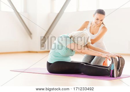 Sport needs hard work. Persistent active aged woman sitting on a yoga mat and leaning forwards while exercising with a female coach